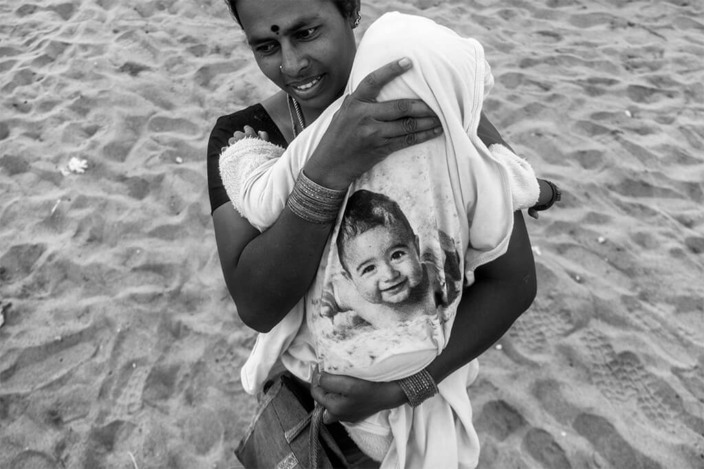 women carrying her baby and enjoying the breeze of chennai shores